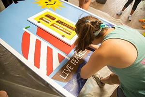 Lily Shaw painting a sign